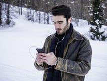 Молодой человек с smartphone в снегах стоковое фото