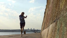 Молодой человек танцует диско и стоит на его руках на речном береге сток-видео