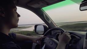 Молодой человек управляет большим мужчиной автомобиля путешествует на сельской местности акции видеоматериалы