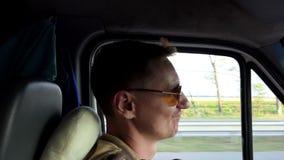 Молодой человек управляет его автомобилем, улыбками и кивками его голова в slo-mo акции видеоматериалы