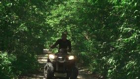 Молодой человек управляет ATV в лесе видеоматериал