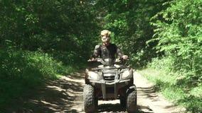 Молодой человек управляет ATV в лесе сток-видео