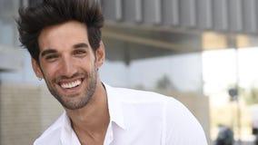Молодой человек усмехаясь к камере нося случайные одежды с современным стилем причесок акции видеоматериалы