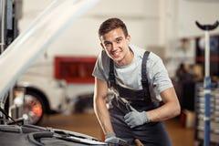 Молодой человек усмехаясь положение около автомобиля на его работе Обслуживание автомобиля и корабля стоковые фотографии rf