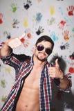 Молодой человек усмехаясь с большими пальцами руки вверх на смешной предпосылке Стоковая Фотография RF