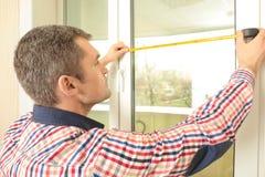 Молодой человек устанавливая рулонные шторы стоковые фотографии rf