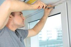 Молодой человек устанавливая рулонные шторы стоковая фотография rf