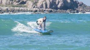 Молодой человек уча заниматься серфингом на океане в Мексике стоковая фотография