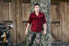 Молодой человек фермера идя на его ферма около деревянного амбара нося красную футболку стоковое фото rf