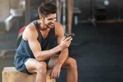 Молодой человек фитнеса сидит на коробке стоковая фотография rf