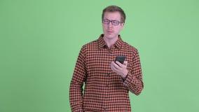 Молодой человек хипстера выпадая из ускорения и используя телефон как карта акции видеоматериалы