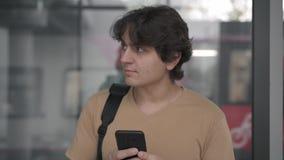 Молодой человек хмурясь и идя прочь смотрящ смартфон на железнодорожном вокзале акции видеоматериалы