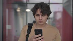 Молодой человек хмурясь смотрящ смартфон на железнодорожном вокзале видеоматериал