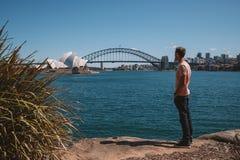 Молодой человек через гавань от оперного театра Сиднея Стоковая Фотография