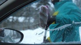 Молодой человек чистит снег щеткой от припаркованного автомобиля в зиме Стоковые Фото