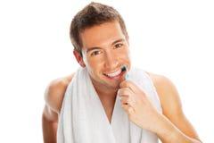 Молодой человек чистя его зубы щеткой Стоковые Изображения