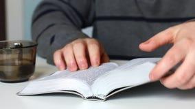 Молодой человек читает библию при серебряный кусок сидя на таблице После этого он закрывает книгу акции видеоматериалы