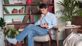 Молодой человек читает книгу пока сидящ в домашней библиотеке, человек в голубой рубашке и джинсы держат книгу и читают видеоматериал