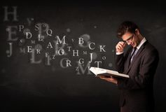 Молодой человек читая книгу с письмами алфавита Стоковые Фотографии RF