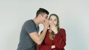 Молодой человек шепча секрету к удивленной молодой женщине Молодой человек говорит секрет к девушке Стоковое фото RF