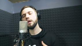 Молодой человек эмоционально записывая новые мелодию или песню Мужская певица в наушниках поя песню в микрофон на звуке акции видеоматериалы