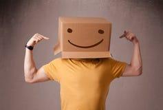 Молодой человек gesturing с картонной коробкой на его головке с smiley Стоковые Фотографии RF