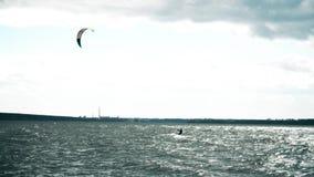 Молодой человек Kitesurfing в океане Весьма восхождение на борт змея в замедленном движении сток-видео
