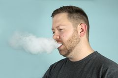 Молодой человек vaping курящ e-сигарету стоковое фото rf