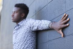 Молодой чернокожий человек нося кенийский браслет флага с рукой протягивает Стоковые Фотографии RF