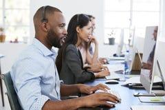Молодой чернокожий человек при шлемофон работая на компьютере в офисе стоковое изображение