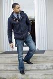 Молодой чернокожий человек стоя на шагах смотря прав Стоковые Фото