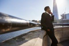Молодой черный бизнесмен нося костюм полагаясь на стене на обваловке Темза, Лондоне, используя смартфон, низкий угол стоковые фото