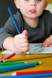 Молодой чертеж мальчика с карандашами на таблице стоковое изображение rf