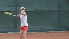 Молодой честолюбивый здоровый образ жизни, серьезная решительная девушка ребенка теннисиста ударяя ракетку на шарике на профессио сток-видео