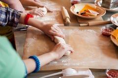 Молодой шеф-повар работая тесто с руками стоковое изображение