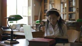 Молодой юрист студентки книга чтения, печатая на компьтер-книжке сидя в библиотеке видеоматериал