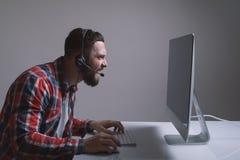 Молодой gamer в наушниках и стеклах используя компьютер для играть игру дома в ноче стоковые фотографии rf