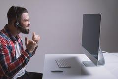 Молодой gamer в наушниках и стекла используя компьютер для играть игру дома празднуют победу стоковое изображение