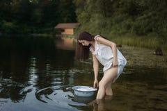 Молодой laundress стоит в реке стоковая фотография rf