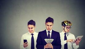 Молодой multitasking бизнесмена используя планшет мобильного телефона подсчитывая деньги Стоковые Изображения