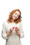 Молодой red-haired счастливый ся подарок удерживания девушки стоковые фото