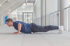 Молодой sporty человек делая нажим поднимает в спортивном центре стоковое фото