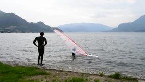 Молодой windsurfer пробуя получить на плавая доске