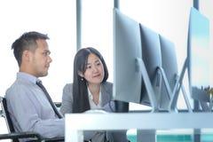 Молодые азиатские бизнесмены работают совместно в современном офисе T стоковая фотография rf