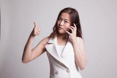 Молодые азиатские большие пальцы руки женщины вверх показывают с жестом телефона Стоковые Фото