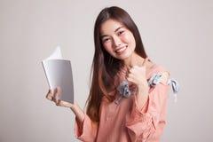 Молодые азиатские большие пальцы руки женщины вверх с книгой Стоковое фото RF
