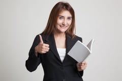 Молодые азиатские большие пальцы руки женщины вверх с книгой Стоковая Фотография RF