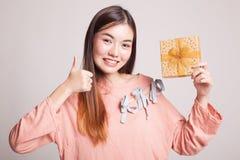 Молодые азиатские большие пальцы руки женщины вверх с подарочной коробкой Стоковая Фотография RF