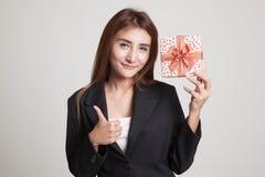 Молодые азиатские большие пальцы руки женщины вверх с подарочной коробкой Стоковое Изображение