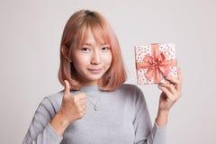 Молодые азиатские большие пальцы руки женщины вверх с подарочной коробкой Стоковые Фотографии RF
